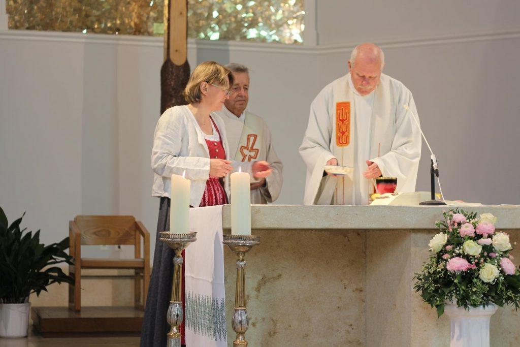 Kommunionsspenderin mit Diakon und Pfarrer am Altar. © Nico Trimmel