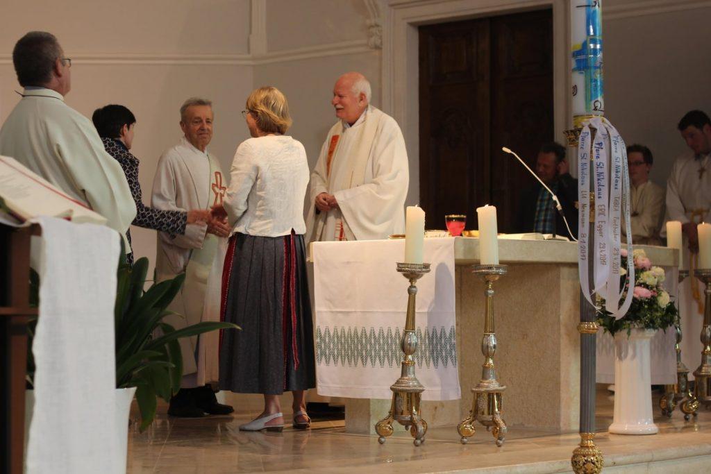 Kommunionsspenderinnen mit Diakon und Pfarrer beim Friedensgruß. © Nico Trimmel